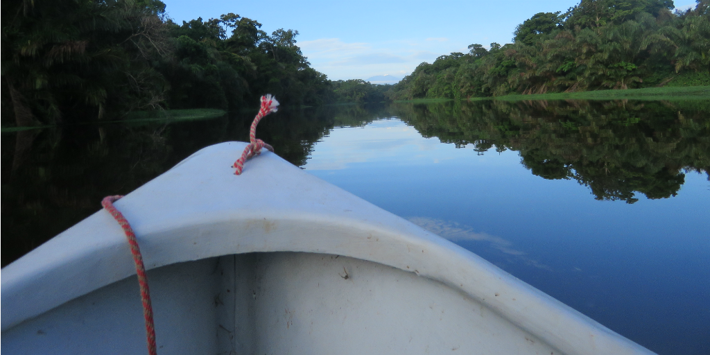 A boat travelling down a river framed by the Costa Rican Rainforest on either side.